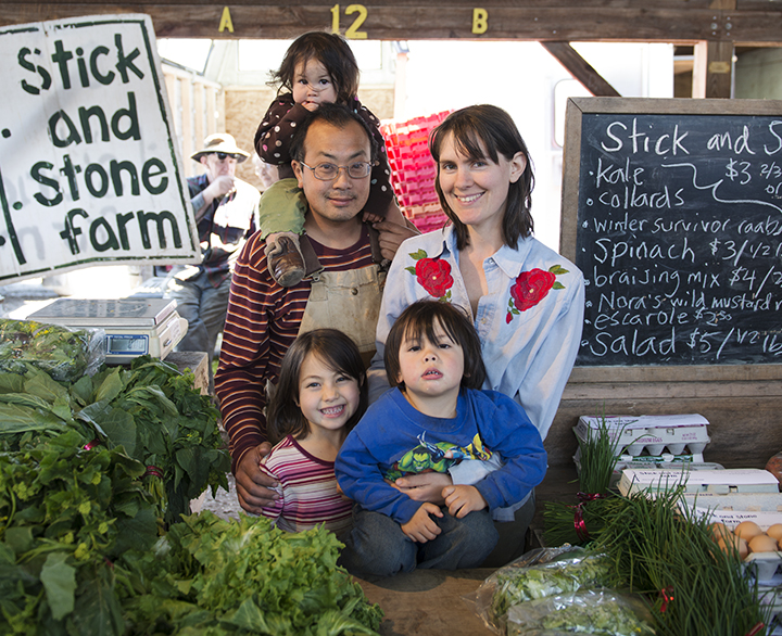 Chaw Chang, Lucy Garrison, and their children: Greta (6), Ezra (3), and Rhoda (1) at the Stick and Stone Farm stall at the Ithaca Farmers Market at Steamboat Landing.